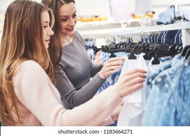 The best friends together spend time. Two beautiful girls make purchases in the clothing store. They dressed in the same clothes.