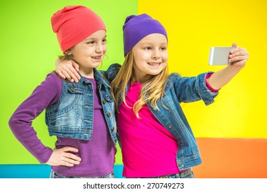 Best friends. Two cute little girls doing selfie on colorful background.