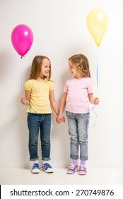 Best friends. Two cute little girls holding balloons on grey background.