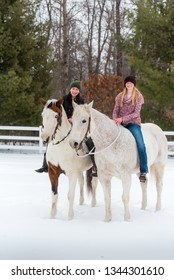 best friends. two girls on their horses bareback along white fence. Winter scene with snow