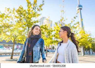 Best friends walking together in Toronto. Two girls studying holding hands and looking each other at park. Friendship and lifestyle concepts.