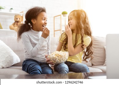 Best friends watching funny cartoon and eating popcorn, sitting on sofa at home