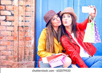 Best friends women taking selfie in funny faces holding shoppers wearing trendy fashion clothes - Girls having fun using phone camera sitting outside on old wall background - Female friendship concept