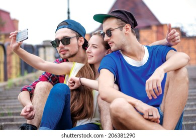 Best friends. Young friends have fun together on the street and smile at each other. Funny guys make Selfie
