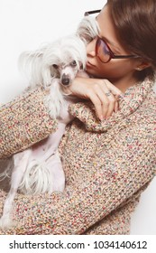 Best girlfriends concept. Young gorgeous lady with natural make-up wearing trendy clothes, eyeglasses kissing small chinese crested dog over white background. Street fashion style. Indoor shot