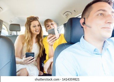 Best girlfriends posting on social media in taxi and texting with friends