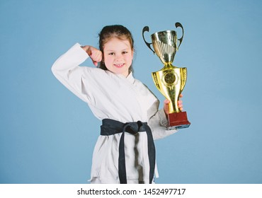 I am the best. knockout. energy and activity for kids. practicing Kung Fu. happy childhood. sport success in single combat. girl with champion cup. martial arts. winner little girl in gi sportswear.