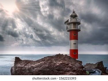 Best Lighthouse Punta de Teno on the Atlantic Ocean - Tenerife. Rocky Coast With Lighthouse, crepuscular rays, sunlight coming from the clouds. Canarian Island / Spain