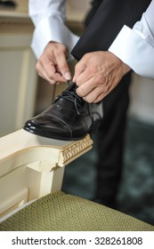 Best man getting ready for a special day. A groom putting on shoes as he gets dressed in formal wear. Groom's suit