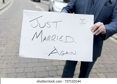 Best man or groom holding a homourous hand written sign stating Just married...again at a second wedding or renewal of vows in the UK