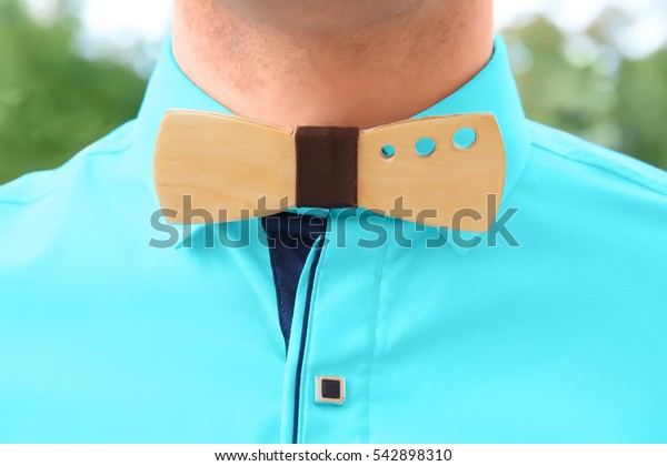 Best man in turquoise shirt with stylish wooden bow tie, close up