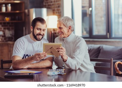 Best memories. Interested attentive unshaken man sitting by the table near a retired smiling and looking at a photo.