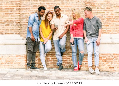 Best multi race friends watching videos surprised on smartphone - Young people having fun with phones outdoors - Technology and internet mobile addiction concept - Warm saturated vintage filter