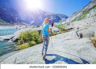 Best Norway hike. Back view of Cute girl with hiking equipment in the mountains. Glacier in the background