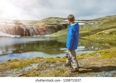 Best Norway hike. Cute boy with hiking equipment in the mountains. Lake in the background