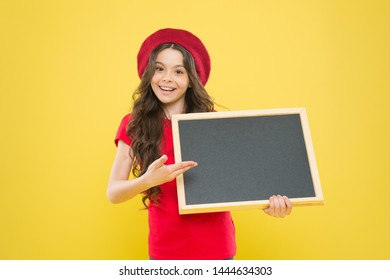 best offer here. board for announcement advertisement. back to school. school shopping sales. kid fashion. happy school girl in parisian beret. little girl kid with backboard, copy space.