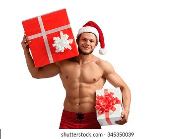 Best part of Christmas. Young sporty man wearing Santa Claus hat smiling cheerfully holding presents
