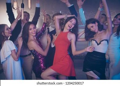 Best party big large mood! Two girls in fabulous dress, skirt dance against funky mood friends with raised hands up and big beaming smile formal wear