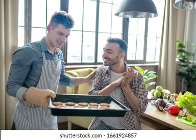 Best pastries. Fair-haired man with a baking sheet showing pastries to a dark-haired young man sitting next to him, both delighted.