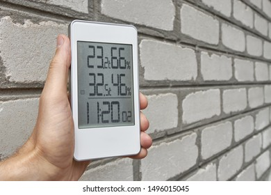 Best personal weather station device with weather conditions inside and outside. A man holds a gadget in his hand against a brick wall.