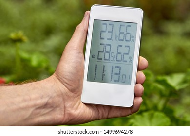 Best personal weather station device with weather conditions inside and outside. A man holds a gadget in her hand on a background of green foliage.