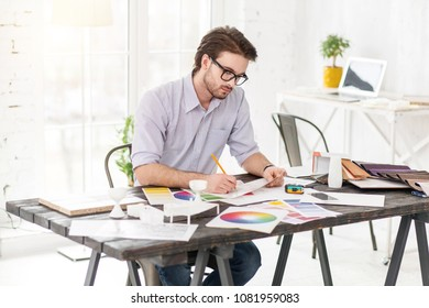 Best profession. Good-looking concentrated man sitting at the table and holding a sheet of paper and a pencil