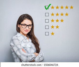 The best rating, evaluation. Business confident happy woman voting to five yellow star to increase ranking. On grey background. Closeup portrait