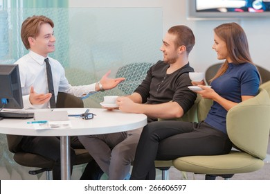 It is a best seller. Smiling sales consultant gesturing and explaining details about the car to the customer couple sitting by the table and drinking coffee