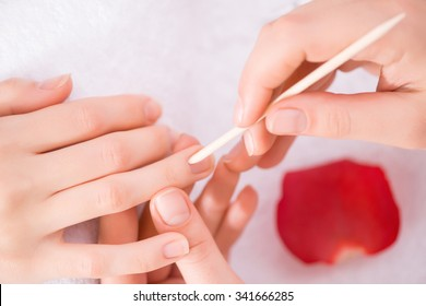 Best service. Close up of cuticle pusher in hands of professional manicurist holding it while making manicure