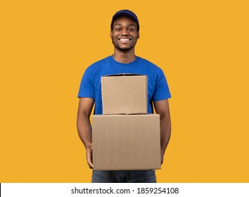 Best Service Concept. Smiling black delivery man in blue cap and unform holding pile of cardboard boxes standing isolated over orange studio background. African american courier carrying packages