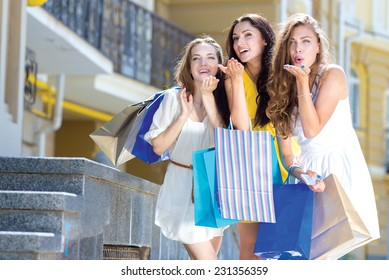 Best shopping wishes. Three young and pretty girls are standing with shopping bags. All are smiling and giving air kisses