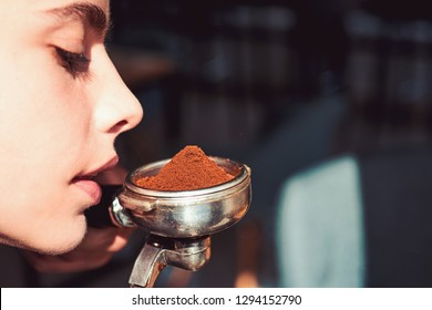 The best smell in the whole wide world. Woman barista hold portafilter in hand. Woman sniff the smell of fresh ground coffee. Barista brew espresso coffee drink. Brewing coffee device.