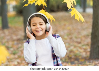 Best song about fall. Cute small child enjoy song playing in headphones. Adorable little girl sing along to song. Autumn leaves song. Music and rhyme.