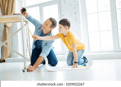 Best team. Cheerful charming young father working on a table construction together while the man measuring the length of a table leg and the boy checking its correctness