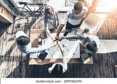 Best team.  Top view of business colleagues holding fists together in a symbol of unity while working in the creative office - Shutterstock ID 1099306394