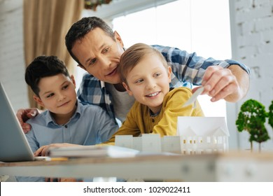 Best tip. Caring young father holding a solar panel miniature and giving his sons a piece of advice regarding it and its use in their ecology project