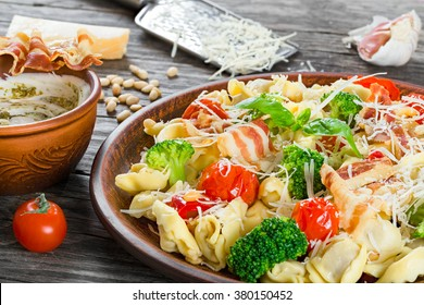 The best Tortellini pasta salad with grilled tomatoes, broccoli, red bell pepper, fried bacon and shredded cheese on a clay brown dish and pesto sauce with greek yogurt in a gravy boat, close-up
