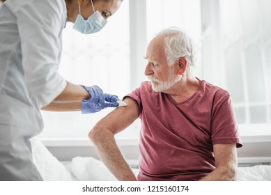 Best treatment for you. Portrait of bearded old man receiving vaccine shot in hand while sitting on hospital bed