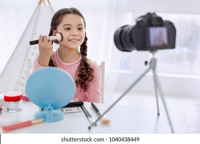 Best tutorial. Cheerful pre-teen girl explaining how to apply powder correctly while making a makeup tutorial for her video blog