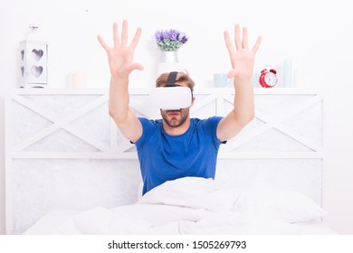 The best VR experience. Handsome guy wearing VR headset in bed. Caucasian man using VR glasses in bedroom. Immersive rendering in VR.