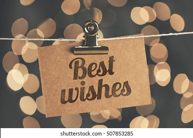 Best wishes sign pegged to a string with blurred bokeh lights in the background