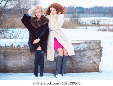 Best womans friends ever. Two young nice girls spending time together at snowy winter park and cuddling on sunny day. Concept of women's friendship and relationship