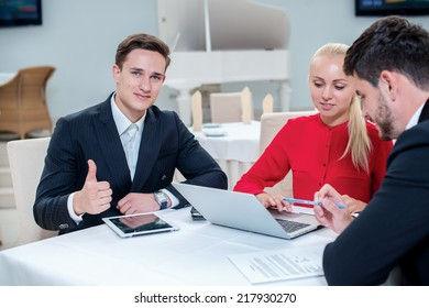 Best work. Three successful businessman discussing work at a laptop. Businesspeople in formal dress sitting in the office at the table and showing thumbs up.