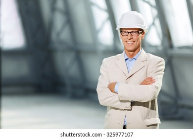 Best worker. Pleasant content confident adult architect folding his hands and expressing positivity while smiling