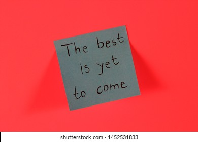 The best is yet to come. Blue sticky note with inspirational quote on neon pink background. Handwritten positive reminder/advice. Concept for confidence, courage and motivation. Sign of moral support.