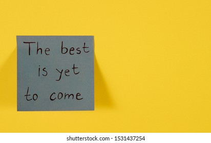 The best is yet to come. Blue sticky note with inspirational quote on neon yellow. Handwritten positive reminder/advice. Concept for confidence, courage and motivation. Sign of moral support.