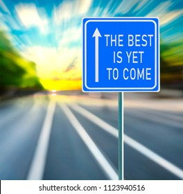The best is yet to come motivational phrase on blue road sign with arrow and blurred speedy background in sunset. Copy space.