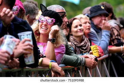 Bestival - 8th September, 2017: Woman wearing black  pussy cat hat in crowd of smiling people at Bestival festival leaning on the barrier. drinking and chatting, Lulworth, Dorset 8 September 2017, UK