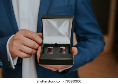 Bestman in blue suit holding box with cufflinks for the grom.