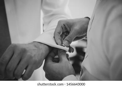 Bestman helping groom to put on cufflinks prior to wedding